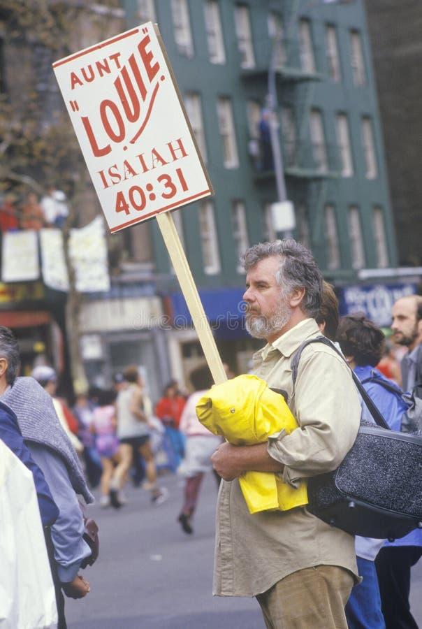 Man on street corner with sign during NY City Marathon, NY royalty free stock image