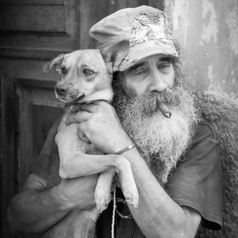 Man on Street, Havana, Cuba. An older man with a cigar and long beard lovingly holds his dog close on the streets of Havana, Cuba stock images