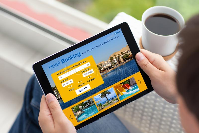 Man in street holding tablet computer with app hotel booking royalty free stock image