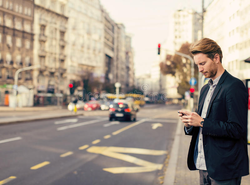 Man on the street with mobile phone. Young man on the street with mobile phone stock images