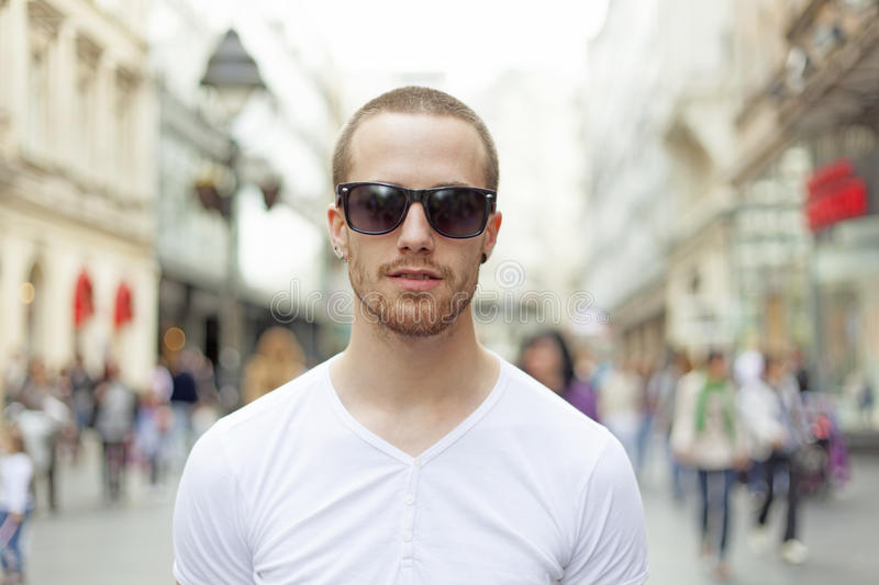 Man on street in white shirt and dark eyeglasses stock photography