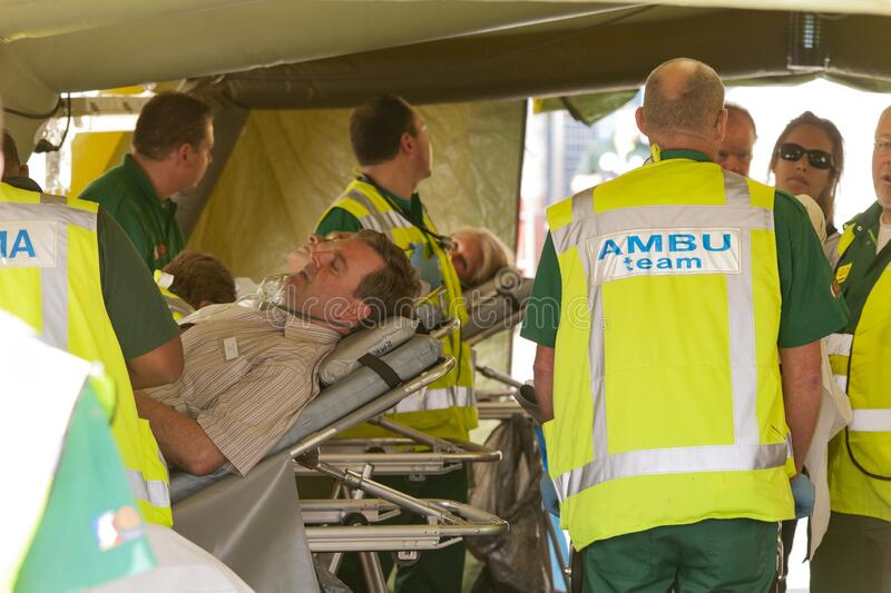 Emergency doctor transporting man on stretcher Vector Image