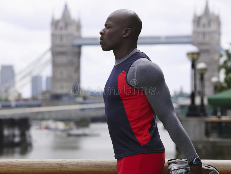 Man Stretching Against Tower Bridge In England stock image