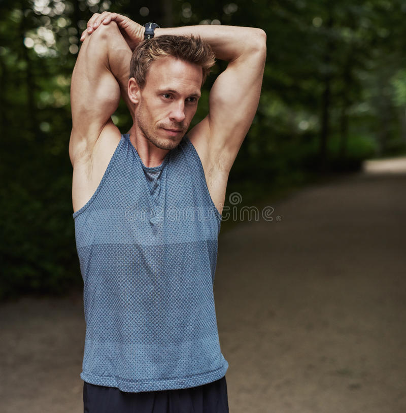 Man Stretching Arms Behind his Head at the Park stock image