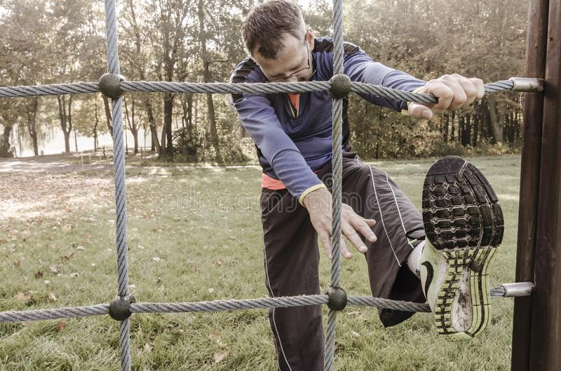 Man stretching on a device in the park before jogging stock photos