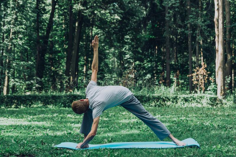 Man stretching hands and legs on green grass in park. royalty free stock photo