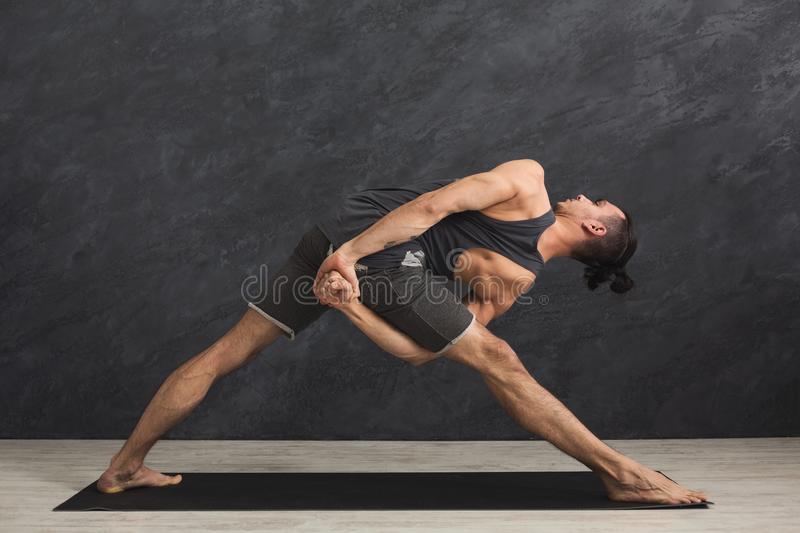 Man stretching hands and legs at gym stock image