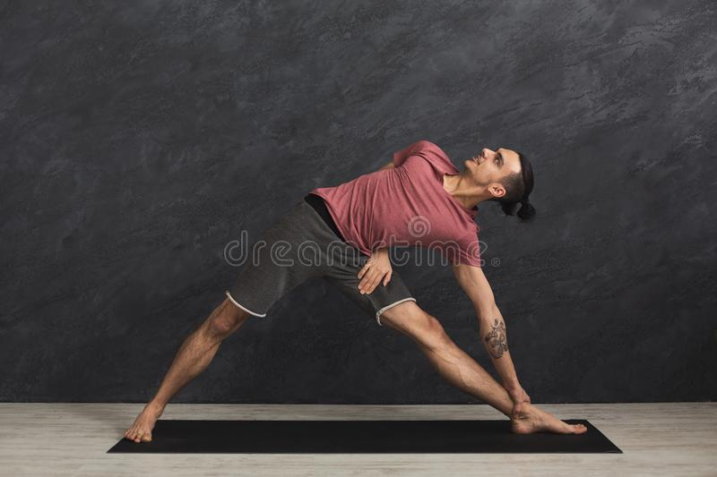Man stretching hands and legs at gym stock photo