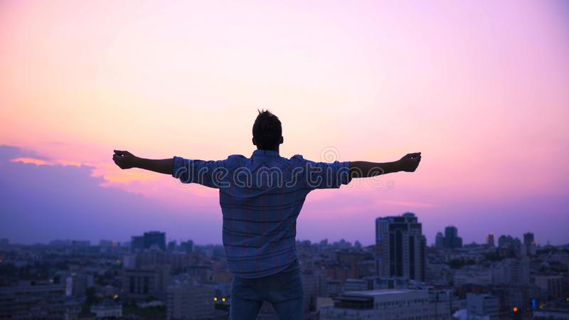 Man stretching hands on roof edge, enjoying freedom, believe in future success royalty free stock image