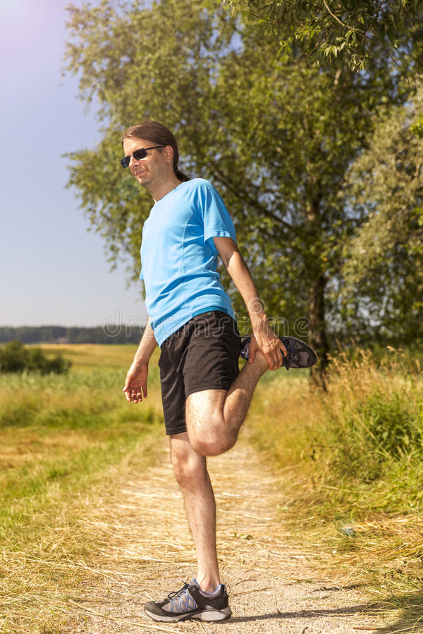 Man stretching after jogging stock images