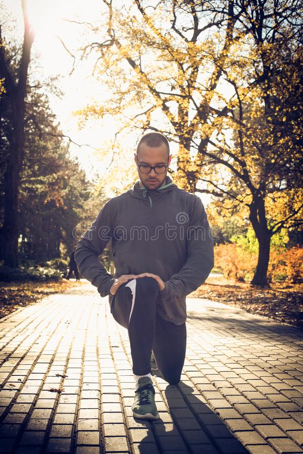 Man stretching lags before exercise. Young sporty man working exercise stock photography