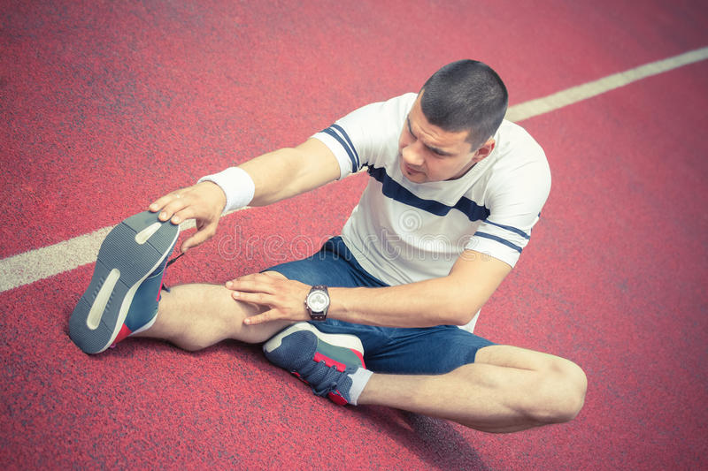 Man stretching leg on the running track. Man stretching hamstring leg muscle on the red running track while preparing for morning workout. Caucasian sport stock images