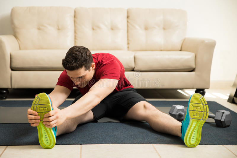 Man stretching and warming up at home. Young man in sporty outfit stretching his legs and warming up before exercising at home royalty free stock image