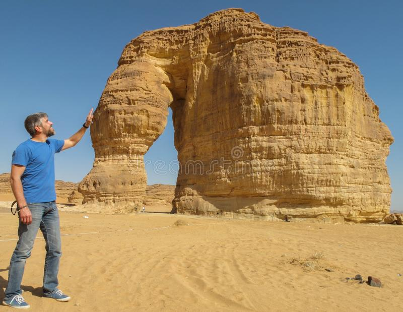 A man stroking the rock formation known as the Elephant Rock in Al Ula, Saudi Arabi KSA stock photo