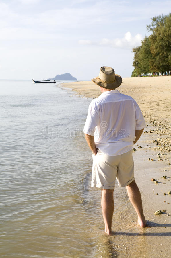 Man strolling on a beach royalty free stock photo