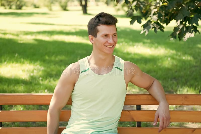 Man with strong hands, biceps, triceps on sunny summer day. Happy sportsman sitting outdoors on natural landscape. Athlete smiling on wooden bench in park royalty free stock image