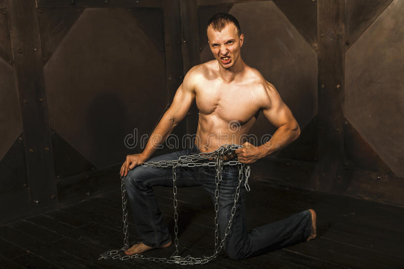 Man with strong muscular arms pulling the chain. Healthy young man with strong muscular arms and torso pulling the chain. Black background. Fitness concept stock image