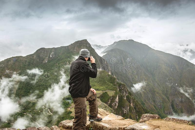 Standing man taking pictures of Machu Picchu stock photo