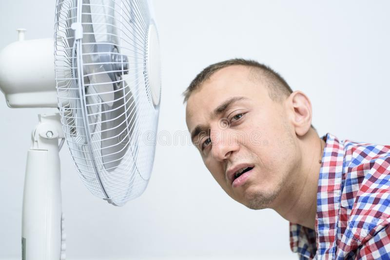 Man with stubble on his face suffers from the heat and trying to cool off near the fan royalty free stock photo