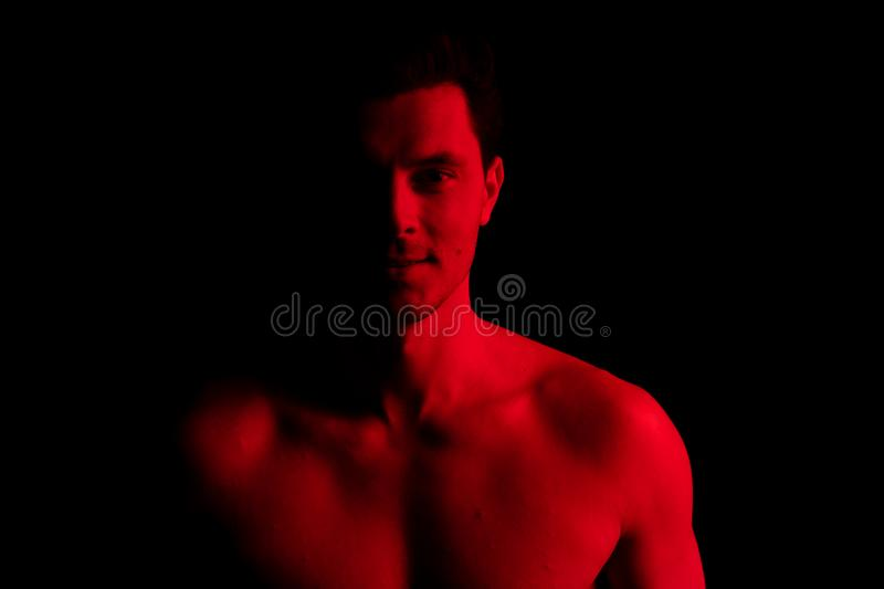 Man in studio with red and blue colors. Look at camera and smile royalty free stock photography