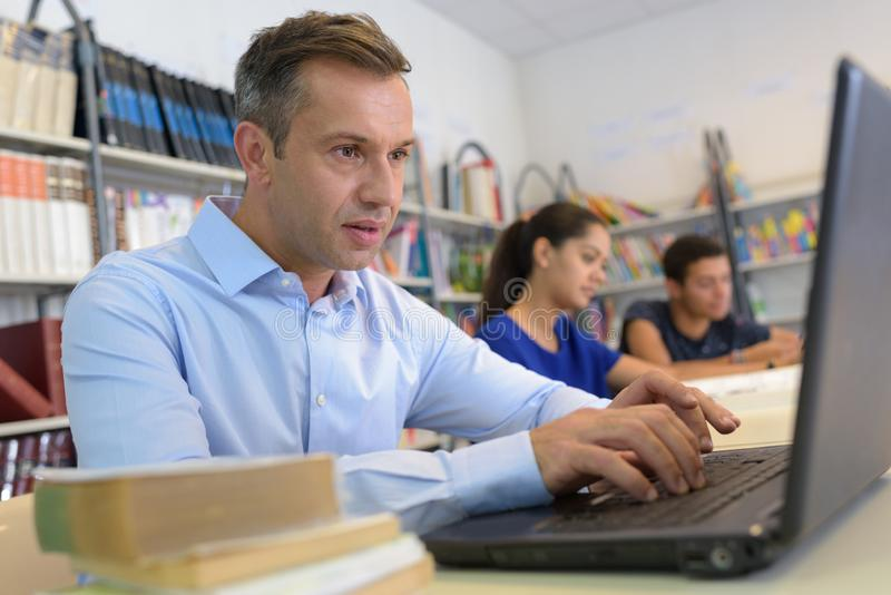 Man studying with laptop computer on white desk stock photos