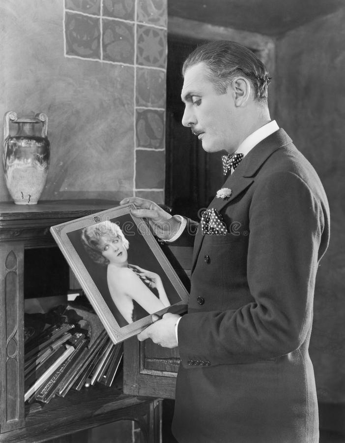 Man studying a picture of a woman. (All persons depicted are no longer living and no estate exists. Supplier grants that there will be no model release issues stock photography