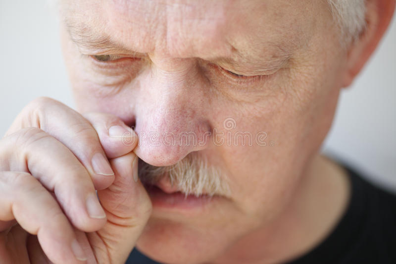 Man with stuffy nose pulls on a nostril. Older man tries to relieve his stopped up nostril royalty free stock photos