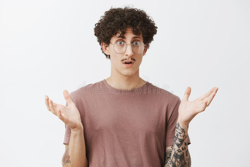 Man in stupor feeling confused cannot understand what happened standing with raised aside palm and opened mouth gazing royalty free stock image
