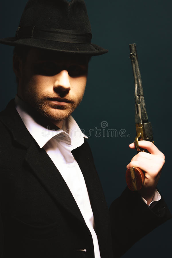 The man in style Chicago gangster. With gun on dark background royalty free stock photos