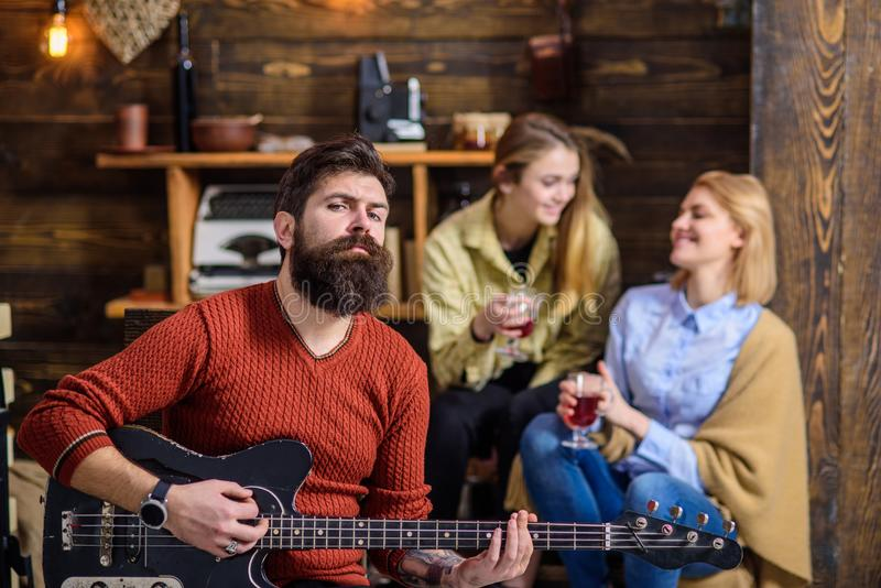 Man with stylish beard enjoying creative process. Musician entertaining his wife and daughter. Girls with smiling face royalty free stock photo