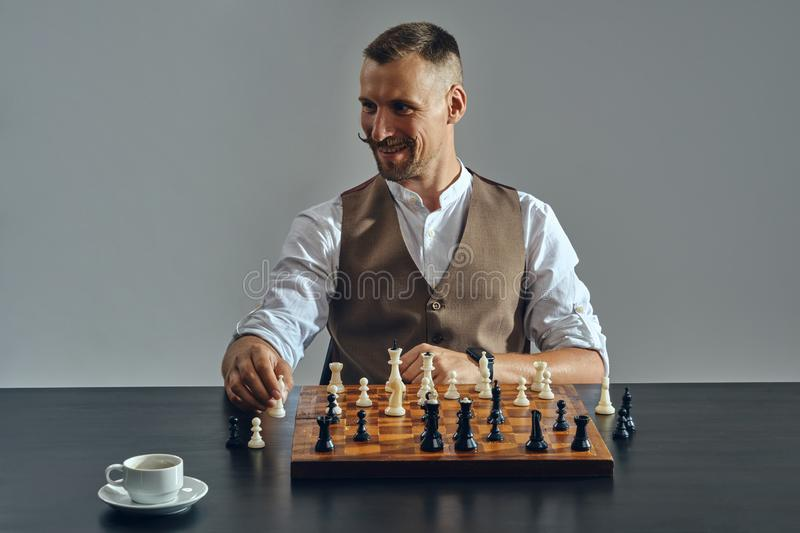 Man with stylish mustache, dressed in brown vest, white shirt is playing chess. Nearby is a cup of coffee. Grey stock images