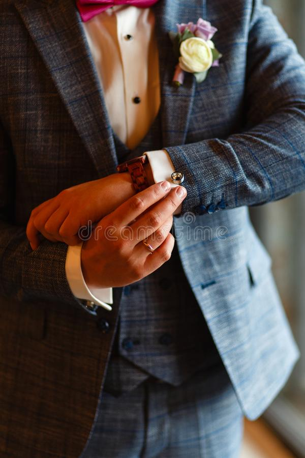 A man in a stylish suit straightens cuffs on his shirt. Shooting of a businessman in a suit. Business concept. Close-up of a man i stock photo