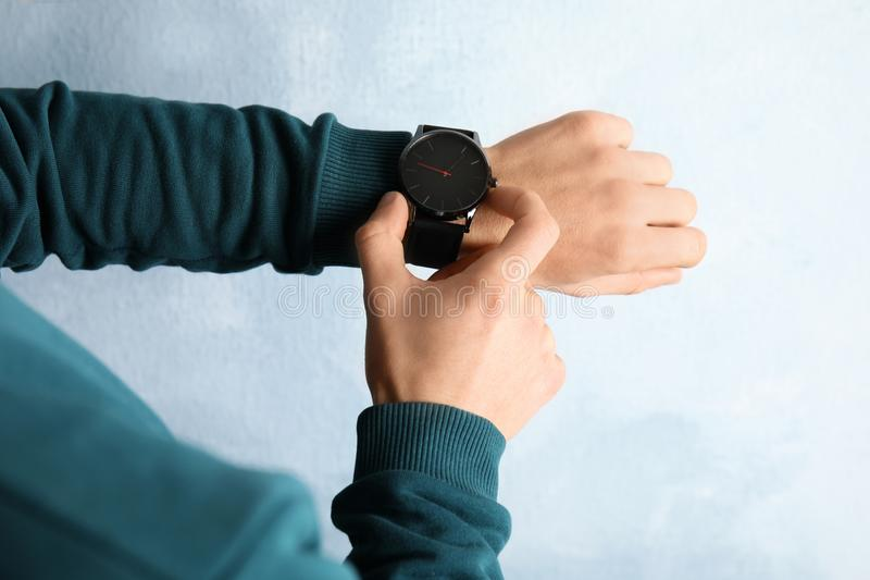 Man with stylish wrist watch on color background, closeup. Time management royalty free stock photography