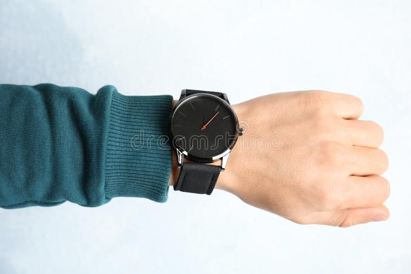 Man with stylish wrist watch on color background. Closeup. Time management stock image