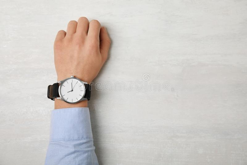 Man with stylish wrist watch at table, space for text. Time management royalty free stock photos