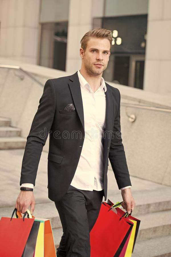 Man stylist professional shopper. Clothes courier. Stylist buy fashionable clothes client. Man formal suit shopping mall. Shop assistant helps carries bunch royalty free stock image
