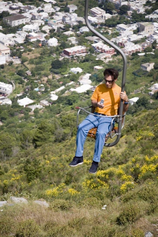 Man su seggiovia che esamina i messaggi di telefono cellulare che trascurano Capri, un'isola italiana fuori dalla penisola di Sor immagine stock libera da diritti