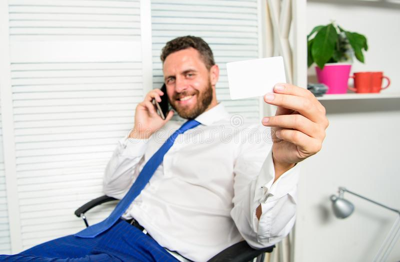 Man successful businessman phone conversation ask service. Businessman bearded guy sit office feel confident. Man hold. Business or bank card copy space. Here royalty free stock photography