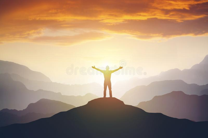 Climber arms up outstretched on mountain top looking at inspirational landscape. stock photo