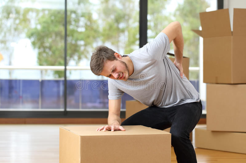 Man suffering back ache moving boxes. In his new house stock photography