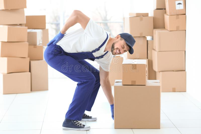 Man suffering from back ache while moving boxes stock image