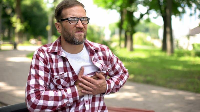 Man suffering chest pain, sitting outdoors, heart arrhythmia, ischemic disease stock photo