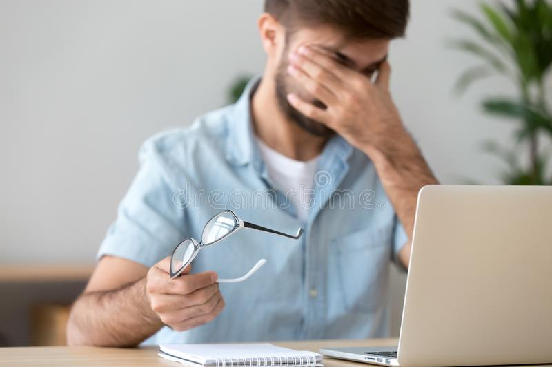 Man suffering from dry eyes syndrome after long computer work. Tired man suffering from dry eyes syndrome after long computer work, taking off glasses, exhausted royalty free stock images