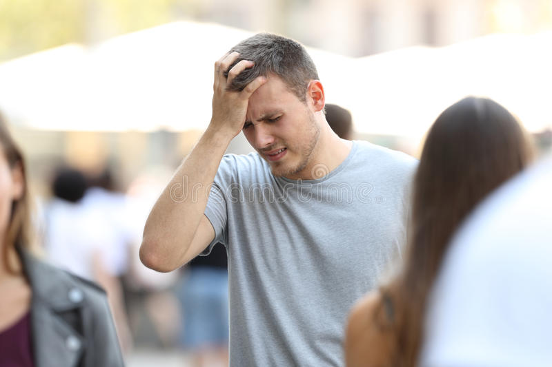 Man suffering head ache on the street. Portrait of a man suffering head ache walking on the street royalty free stock images