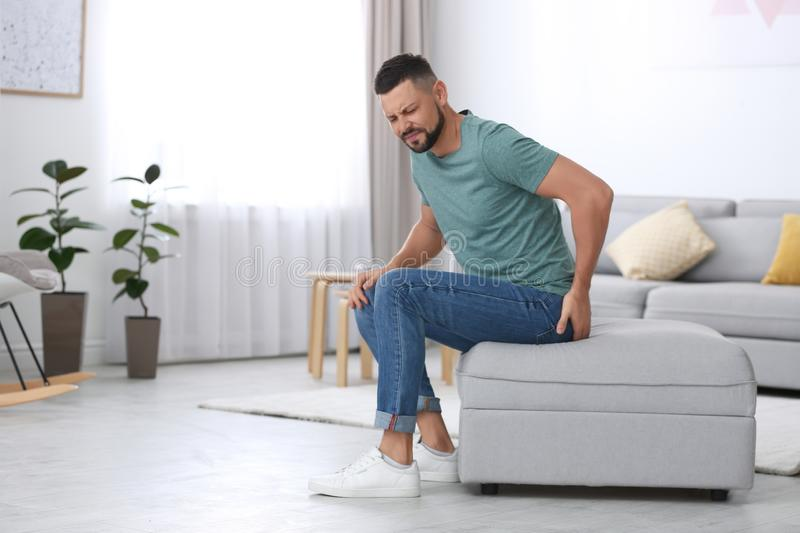 Man suffering from hemorrhoid in room. Space for text stock photography