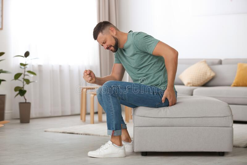 Man suffering from hemorrhoid in room royalty free stock image