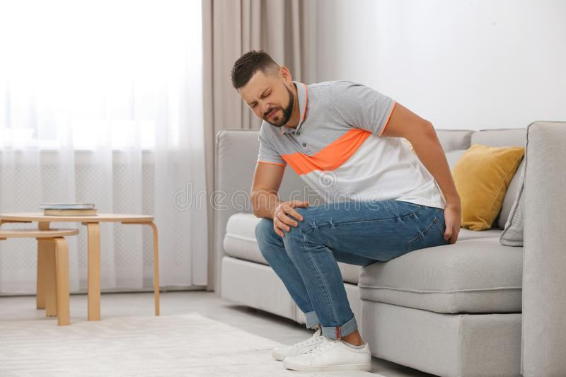 Man suffering from hemorrhoid on sofa royalty free stock image