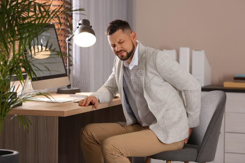 Man suffering from hemorrhoid at workplace royalty free stock photos