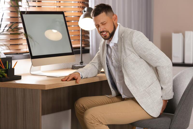 Man suffering from hemorrhoid at workplace royalty free stock images