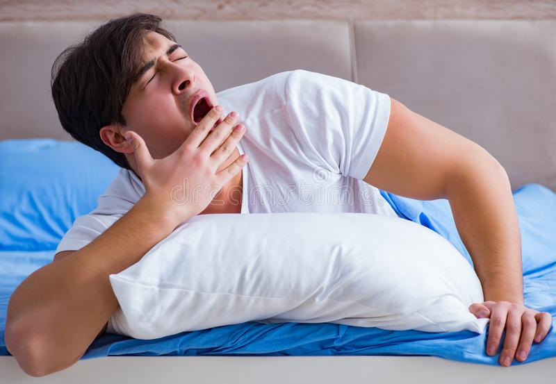 Man suffering from insomnia lying in bed royalty free stock photography